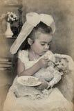 Το μικρό κορίτσι ταΐζει την κούκλα της Στοκ φωτογραφία με δικαίωμα ελεύθερης χρήσης