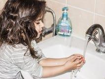 Το μικρό κορίτσι την πλένει παραδίδει το λουτρό κάτω από το τρεχούμενο στοκ φωτογραφία με δικαίωμα ελεύθερης χρήσης