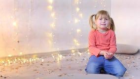 Το μικρό κορίτσι της ευρωπαϊκής εμφάνισης κάθεται στο πάτωμα στο στούντιο φωτογραφιών με το νέο ντεκόρ έτους ` s απόθεμα βίντεο