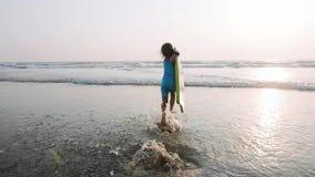 Το μικρό κορίτσι τρέχει στη θάλασσα στα κύματα που κρατούν την ιστιοσανίδα στα χέρια της απόθεμα βίντεο