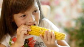 Το μικρό κορίτσι τρώει ένα βρασμένο καλαμπόκι απόθεμα βίντεο