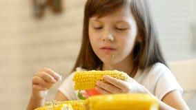 Το μικρό κορίτσι τρώει ένα βρασμένο καλαμπόκι φιλμ μικρού μήκους