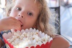 Το μικρό κορίτσι τρώει γλυκό popcorn Στοκ φωτογραφία με δικαίωμα ελεύθερης χρήσης