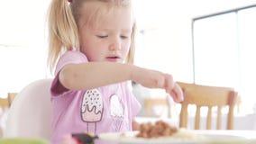 Το μικρό κορίτσι τρώει στον καφέ φιλμ μικρού μήκους