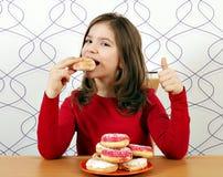 Το μικρό κορίτσι τρώει τα γλυκά donuts Στοκ εικόνα με δικαίωμα ελεύθερης χρήσης