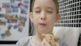 Το μικρό κορίτσι τρώει τα μπισκότα μελοψωμάτων καθμένος στην κουζίνα Χειμερινές διακοπές απόθεμα βίντεο