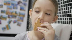 Το μικρό κορίτσι τρώει τα μπισκότα μελοψωμάτων καθμένος στην κουζίνα οι διακοπές αγοριών βάζουν το χειμώνα χιονιού φιλμ μικρού μήκους
