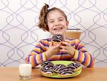 Το μικρό κορίτσι τρώει τη γλυκιά σοκολάτα donuts Στοκ φωτογραφία με δικαίωμα ελεύθερης χρήσης