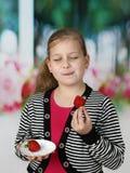 Το μικρό κορίτσι τρώει τη φράουλα στοκ φωτογραφίες