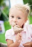 το μικρό κορίτσι τρώει το κέικ Στοκ Φωτογραφία