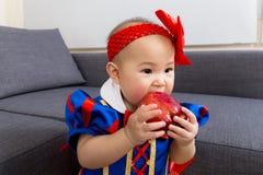 Το μικρό κορίτσι τρώει το μήλο στοκ εικόνες