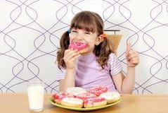 Το μικρό κορίτσι τρώει donuts Στοκ φωτογραφίες με δικαίωμα ελεύθερης χρήσης