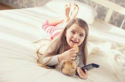 Το μικρό κορίτσι τρώει oatmeal τα μπισκότα στο κρεβάτι Στοκ Φωτογραφίες