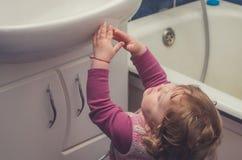 Το μικρό κορίτσι φθάνει για το νεροχύτη στο λουτρό Στοκ Φωτογραφία