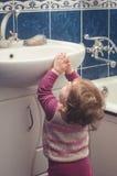 Το μικρό κορίτσι φθάνει για το νεροχύτη στο λουτρό Στοκ φωτογραφία με δικαίωμα ελεύθερης χρήσης