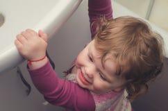 Το μικρό κορίτσι φθάνει για το νεροχύτη στο λουτρό Στοκ Φωτογραφίες
