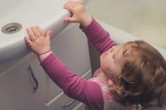 Το μικρό κορίτσι φθάνει για το νεροχύτη στο λουτρό Στοκ Εικόνες