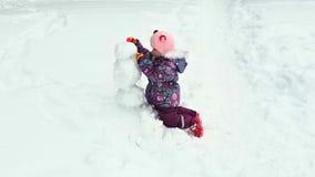 Το μικρό κορίτσι φορμάρει το χιονάνθρωπο απόθεμα βίντεο