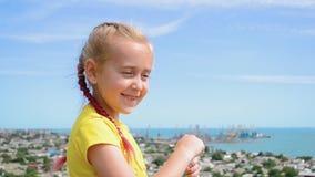 Το μικρό κορίτσι φυσά τις φυσαλίδες σαπουνιών στο υπόβαθρο της πόλης κ απόθεμα βίντεο