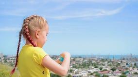 Το μικρό κορίτσι φυσά τις φυσαλίδες σαπουνιών στο υπόβαθρο της πόλης κ φιλμ μικρού μήκους
