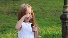 Το μικρό κορίτσι φυσά τις φυσαλίδες κοντά στα σκαλοπάτια στο πράσινο πάρκο απόθεμα βίντεο