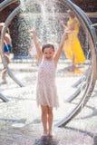 Το μικρό κορίτσι φωτεινά sundress χαίρεται τις πτώσεις της πηγής πόλεων στοκ φωτογραφίες με δικαίωμα ελεύθερης χρήσης