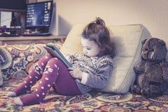 Το μικρό κορίτσι χρησιμοποιεί μια ψηφιακή ταμπλέτα στο σπίτι Στοκ εικόνα με δικαίωμα ελεύθερης χρήσης