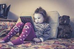 Το μικρό κορίτσι χρησιμοποιεί μια ψηφιακή ταμπλέτα στο σπίτι Στοκ φωτογραφίες με δικαίωμα ελεύθερης χρήσης