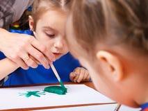 Το μικρό κορίτσι χρωματίζει με μια γκουας στοκ εικόνες