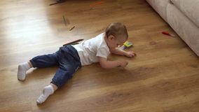Το μικρό κορίτσι χρωματίζει στο πάτωμα με τα κραγιόνια απόθεμα βίντεο