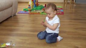 Το μικρό κορίτσι χρωματίζει στο πάτωμα με τα κραγιόνια φιλμ μικρού μήκους