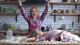 Το μικρό κορίτσι όλα βρώμικα με το αλεύρι ξαπλώνει στον υψηλό πίνακα κουζινών και η ξανθή όμορφη μητέρα ψεκάζει την κόρη με φιλμ μικρού μήκους