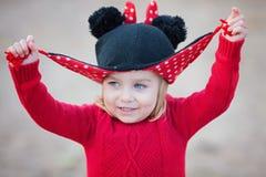 Το μικρό κορίτσι δύο χρονών που έχει το παιχνίδι διασκέδασης κρυφοκοιτάζει ένα boo με το καπέλο της Πορτρέτο Στοκ φωτογραφία με δικαίωμα ελεύθερης χρήσης