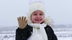 Το μικρό κορίτσι $cu σε ένα άσπρο πλεκτό καπέλο που χαμογελά υπέροχα την εξέταση τη κάμερα, αυτό χιονίζει στην οδό, κοιτάζει φιλμ μικρού μήκους