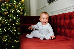 Το μικρό μωρό κάθεται στον καναπέ, στα πλαίσια ενός χριστουγεννιάτικου δέντρου στοκ εικόνες με δικαίωμα ελεύθερης χρήσης