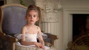 Το μικρό ξανθομάλλες κορίτσι κάθεται σε μια καρέκλα σε μια εστία σε ένα άσπρο tutu ballerina διδάσκει τις μικρές μαθήτριες φιλμ μικρού μήκους