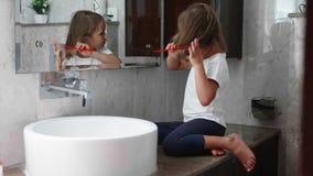 Το μικρό ξανθό κορίτσι κτενίζει τις τρίχες της μπροστά από τον καθρέφτη στο λουτρό απόθεμα βίντεο