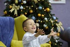 Το μικρό παιδί έχει τη διασκέδαση στο υπόβαθρο του χριστουγεννιάτικου δέντρου στοκ φωτογραφία