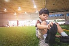 Το μικρό παιδί αλλάζει τα παπούτσια του που παίρνουν έτοιμα για το ποδόσφαιρο Στοκ εικόνες με δικαίωμα ελεύθερης χρήσης