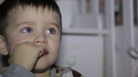 Το μικρό παιδί εξετάζει την οθόνη TV στην αιφνιδιαστική συνεδρίαση σε μια καρέκλα στο δωμάτιο απόθεμα βίντεο