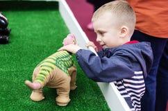 Το μικρό παιδί επικοινωνεί με ένα παιχνίδι ρομπότ σε μια έκθεση σε ένα εμπορικό κέντρο Στοκ φωτογραφία με δικαίωμα ελεύθερης χρήσης