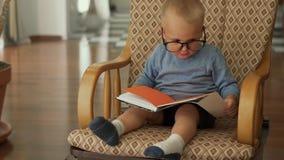 Το μικρό παιδί κάθεται με ένα βιβλίο σε μια καρέκλα απόθεμα βίντεο