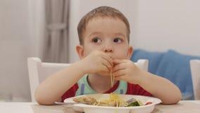 Το μικρό παιδί κάθεται σε έναν πίνακα σε έναν τον ετερόφθαλμο γάδο και τρώει τα μακαρόνια του, το χαριτωμένο μωρό τρώει πρόθυμα μ φιλμ μικρού μήκους