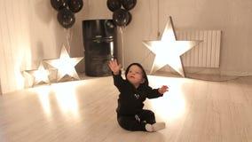 Το μικρό παιδί κάθεται στο πάτωμα στούντιο σε ένα κλίμα των καμμένος αστεριών απόθεμα βίντεο