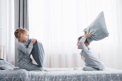 Το μικρό παιδί και το κορίτσι οργάνωσαν μια πάλη μαξιλαριών στο κρεβάτι στην κρεβατοκάμαρα Τα άτακτα παιδιά κτυπούν το ένα το άλλ στοκ φωτογραφία με δικαίωμα ελεύθερης χρήσης
