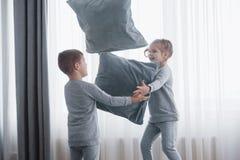 Το μικρό παιδί και το κορίτσι οργάνωσαν μια πάλη μαξιλαριών στο κρεβάτι στην κρεβατοκάμαρα Τα άτακτα παιδιά κτυπούν το ένα το άλλ στοκ φωτογραφίες με δικαίωμα ελεύθερης χρήσης