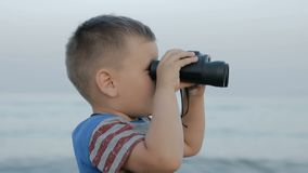Το μικρό παιδί κοιτάζει μέσω των διοπτρών απόθεμα βίντεο
