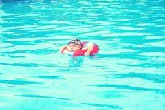 Το μικρό παιδί κολυμπά, εύθυμο άλμα παιδιών στη λίμνη στον κύκλο, υπαίθρια πισίνα, στοκ εικόνα με δικαίωμα ελεύθερης χρήσης