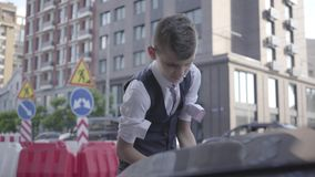 Το μικρό παιδί κυλά επάνω τα μανίκια και αυξάνει την κουκούλα του αυτοκινήτου Βέβαιο αγόρι που πηγαίνει να καθορίσει το αυτοκίνητ απόθεμα βίντεο