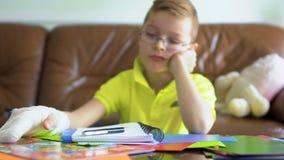 Το μικρό παιδί με το σπασμένο χέρι φορά ` τ θέλει να κάνει τη σχολική εργασία του απόθεμα βίντεο